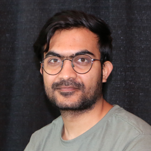 Udaykumar Posia (he/him) Junior Developer poses for his staff photo. Behind him is a black curtain.