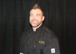 Ryan Katchuk (he/him) URSU Kitchen Manager sits in front of a black curtain for a staff photo. He is wearing a black chef's jacket with his name and Executive Chef on it.
