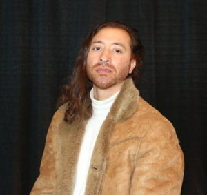 Edgar Martinez (he/him) URSU Graphic Designer poses for his staff photo. His luxurious hair falls over his right shoulder, hi is wearing a stylish tan suede jacket and white turtleneck.
