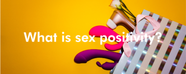 """A basket of sex toys spills out on to a yellow background with text that reads """"What is sex positivity?"""""""