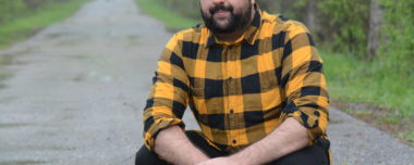 IMAGE DESCRIPTION: Outdoors Mohammad Talha Akbar crouches on a tree-lined path while looking at the camera.
