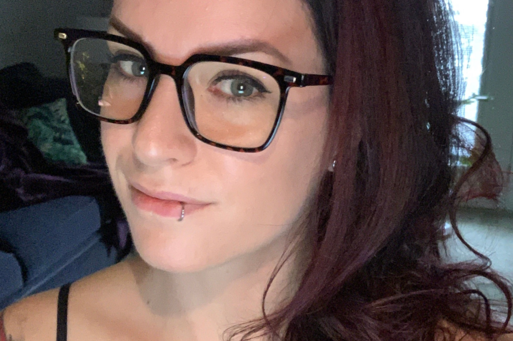 Taryn is wearing glasses and looking toward the camera out of the corner of their eye- they have a lip piercing and a slight smile on their face.