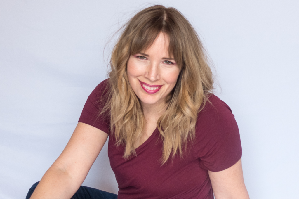 robin is wearing a burgundy shirt, sitting on the ground with a white background. She's smiling directly at the camera.