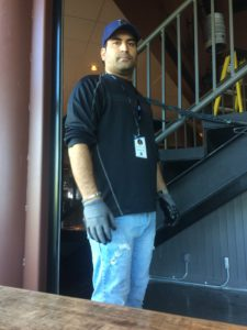 Hadi Akhoondzade (he/him) URSU Maintenance Coordinator stands next to a stairwell indoors at The Lazy Owl.